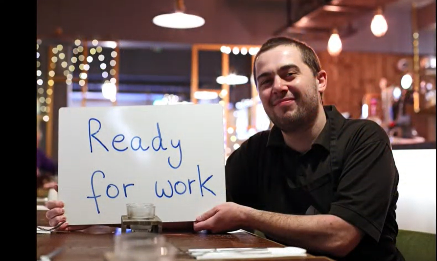 Man holding sign saying ready for work